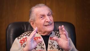 Ein Mann mit schütterem grau-weißen Haar und Schnauzbart sitzt auf einem dunkelbraunen Ledersessel und gestikuliert.