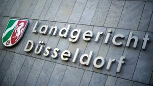 """Auf einer grauen Steinfassade ist ein Schild mit dem Wappen von Nordrhein-Westfalen und der Schriftzug """"Landgericht Düsseldorf"""""""