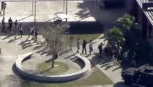 In einer Reihe überqueren Schüler mit erhobenen Händen den Schulhof der Marjory Stoneman Douglas High School