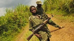 Ein schwarzer Junge in Uniform und mit einer AK47 steht auf einem Feldweg
