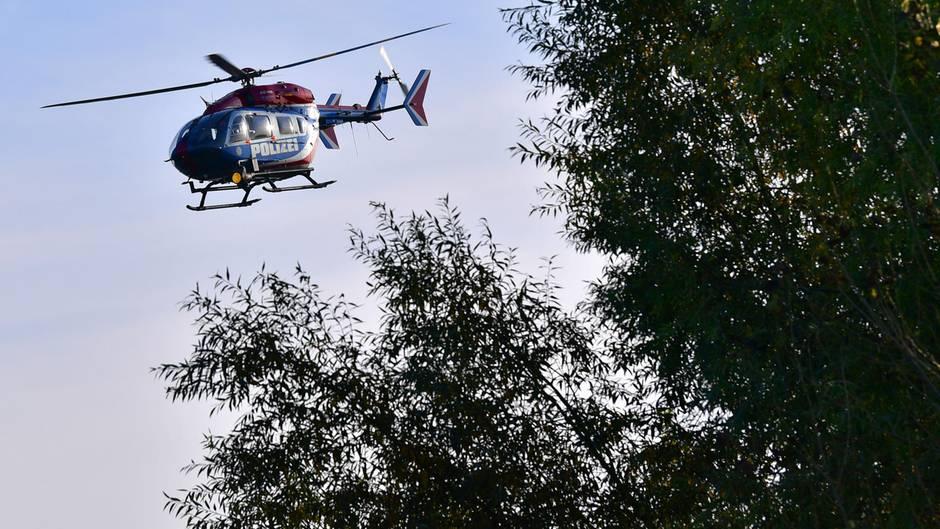 Ein Hubschrauber fligt über Baumwipfel