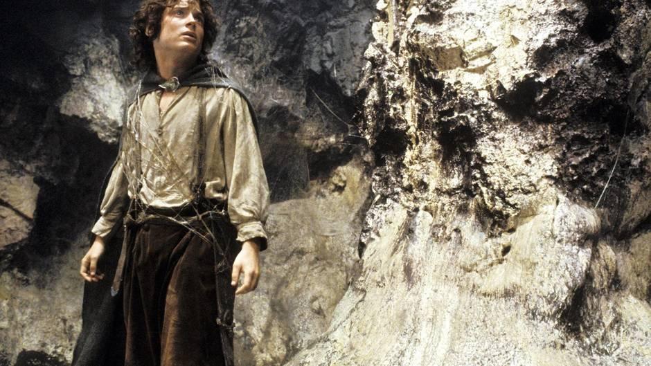 """Frodo – der Hobbit aus """"Der Herr der Ringe"""" steht vor einer Felswand"""