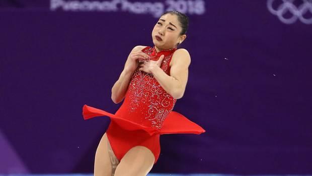 Eine Eiskunstläuferin springt in die Höhe