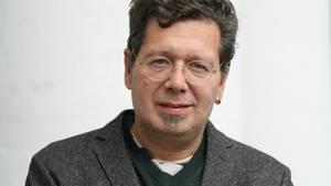 Mit Seitenscheitel und runder Brille blickt der Schriftsteller Franzobel in die Kamera. Er trägt ein Wolljackett