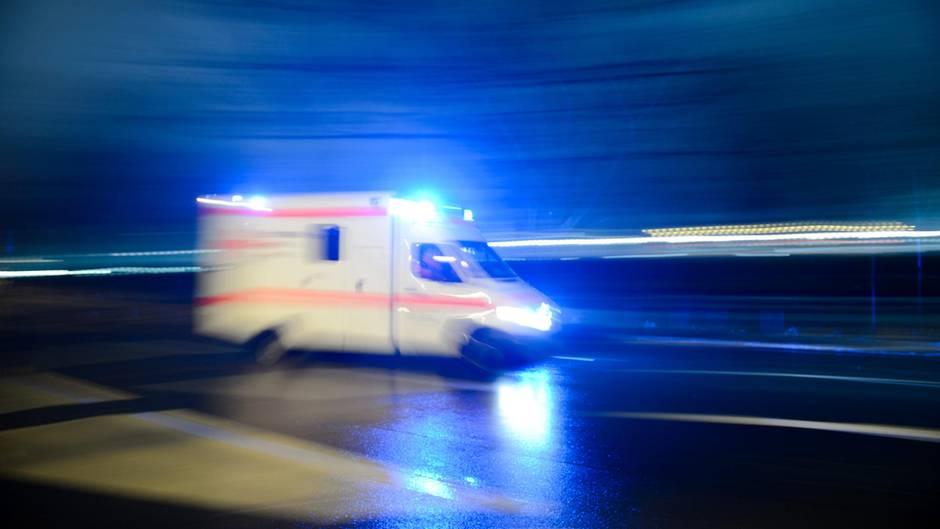 Ein Krankenwagen fährt mit Blaulicht durch eine dunkle, regennasse Straße in Berlin. Das Bild hat Bewegungsunschärfe