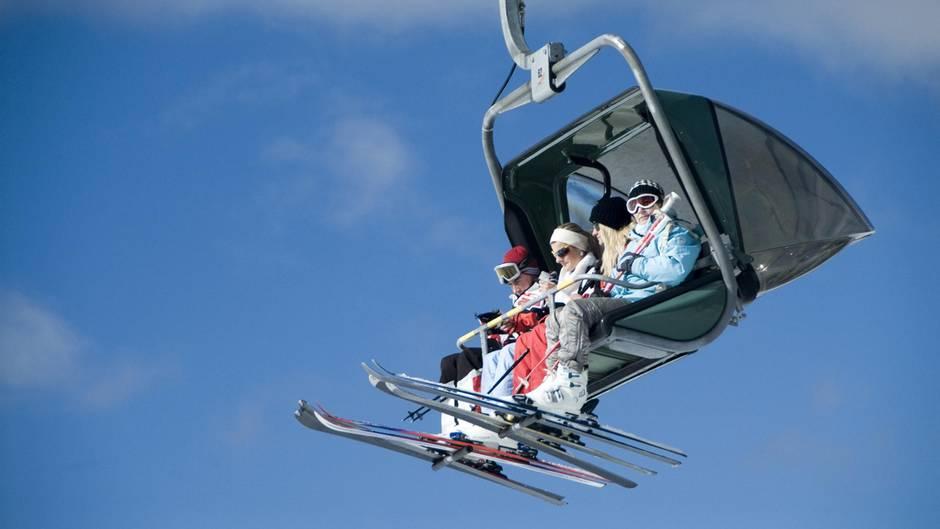 Vier Skifahrerinnen und Skifahrer sitzen in einem Vierer-Sessellift, am Himmel nur Schleierwölkchen