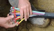Ein Bauarbeiter kniet in einem Erdloch und hält in seinen Händen einen Strang mit unterschiedlich farbig markierten Kabeln
