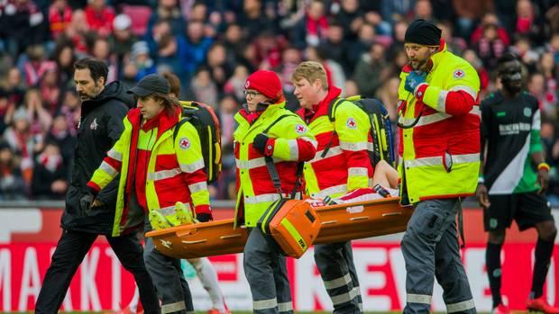 Vier Sanitäter tragen auf einer Trage Simon Terodde vom 1. FC Köln vom Platz, nachdem der einen Tritt an den Kopf bekommen hat
