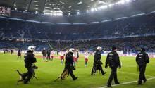 Behelmte Polizei-Hundführer marschieren zwischen HSV-Spielern und den Fans auf