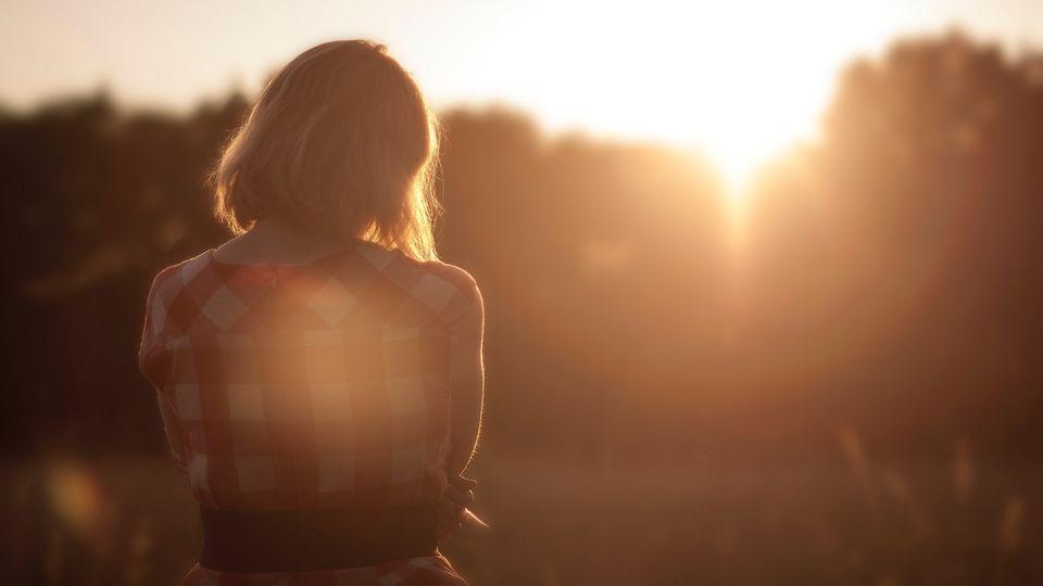 Frau blickt auf bei Sonnenaufgang auf ein Feld
