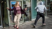 Ein Mann klaut einer Frau eine Handtasche