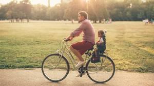 Ein guter Fahrrad-Kindersitz hilft, das Kind sicher durch den Verkehr zu manövrieren. Dieser Papa hat allerdings den Helm vergessen.