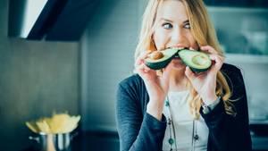 Eine junge Frau beißt in eine Avocado
