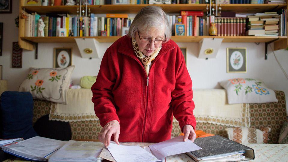 Marlies Krämer such in ihrer Wohnung nach einem Dokument.