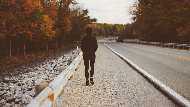 Frau läuft an einer Landstraße im Wald entlang