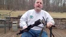 Ein älterer Mann mit Jeans und grauem Sweatshirt sitzt mit seiner zersägten AR-15 in den Händen auf einer Terrasse