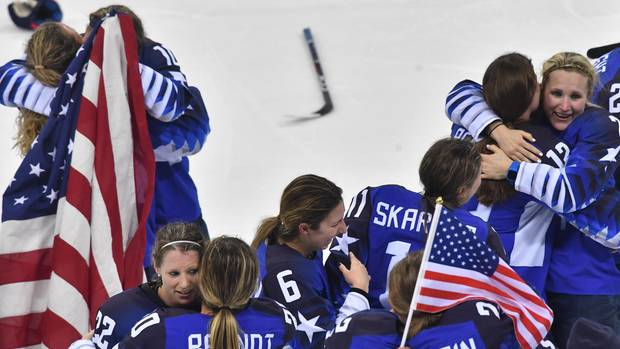 Ohne Helme, aber mit US-Flaggen in den Händen feiern die Damen des Eishockey-Teams der USA ihre Goldmedaille