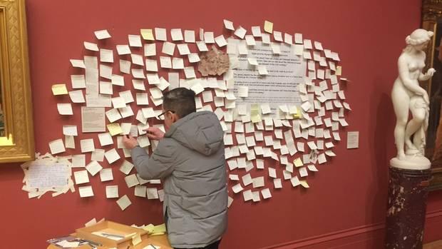 Ein Mann klebt eine Haftnotiz an die Museumswand in der Manchester Art Gallery.