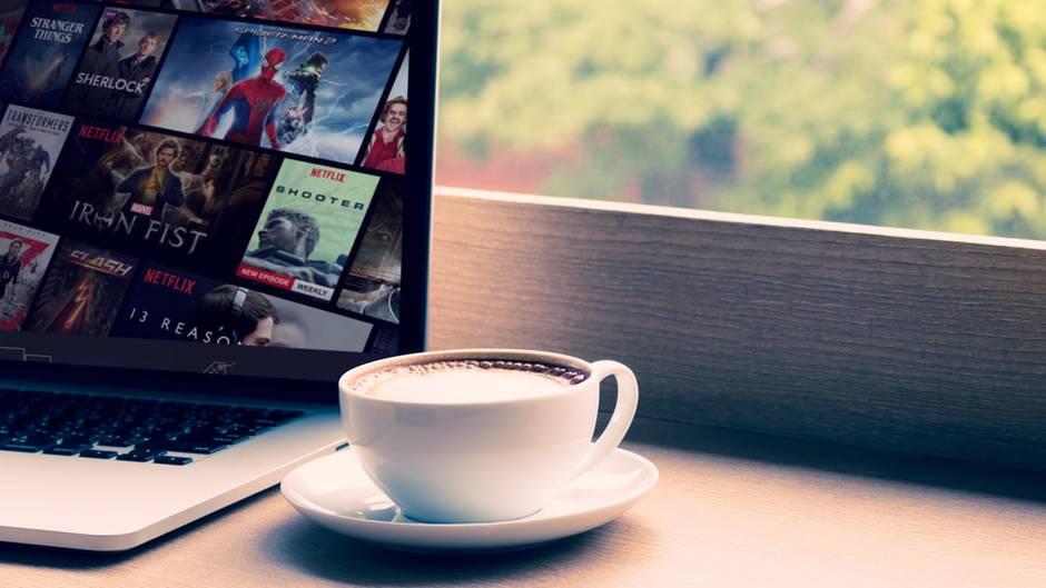 Eine Tasse Kaffee steht neben einem Laptop, auf dem das Streaming-Angebot von Netflix geöffnet ist.
