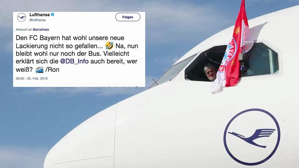 Ein Pilot hält eine Bayern-Flagge aus einem Lufthansa-Flugzeug