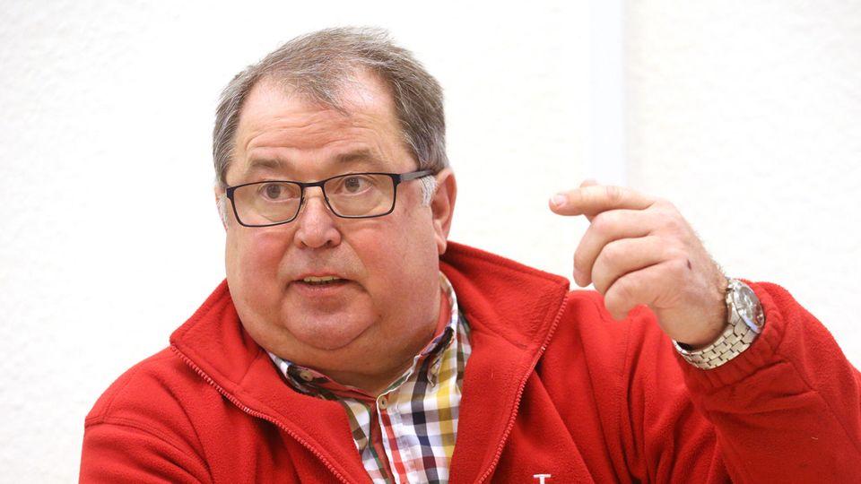 Jörg Sartor, ein kräftiger Mann mit grauem Seitenscheitel, schwarzer Brille und in roter Fleecejacke, gestikuliert
