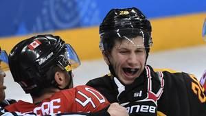 An die Gurgel: Die Kanadier sind mächtig in Rage, als sie gegen die Deutschen im Eishockey-Halbfinale auf die Verliererstraße geraten. Maxim Lapierre (l.) greift dem Deutschen Frank Mauer sogar an die Gurgel.