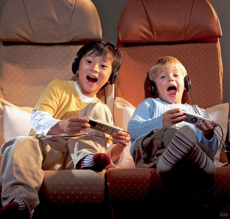 Abgelenkt durch das Unterhaltungsprogramm an Bord: Kids mit der Fernbedienung in Händen.