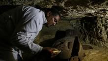 Ein ägyptischer Archäologe arbeitet in einer kürzlich entdeckten Nekropole an einem Sarkophag.