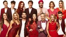 """Die prominenten Kandidaten von """"Let's Dance"""" bei RTL stehen in Rottönen gekleidet auf einem Gruppenbild zusammen"""