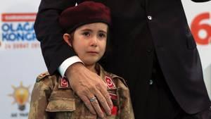 Der türkische Präsident Recep Tayyip Erdogan mit einem weinenden Mädchen in Militäruniform