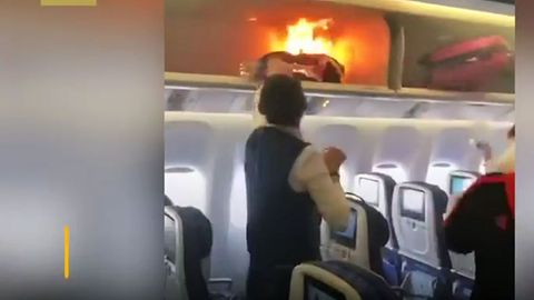 Im Handgepäckfach über die Sitzen brennt die Tasche eines Passagiers an bord einer Boeing 777 der China Southern Airlines.
