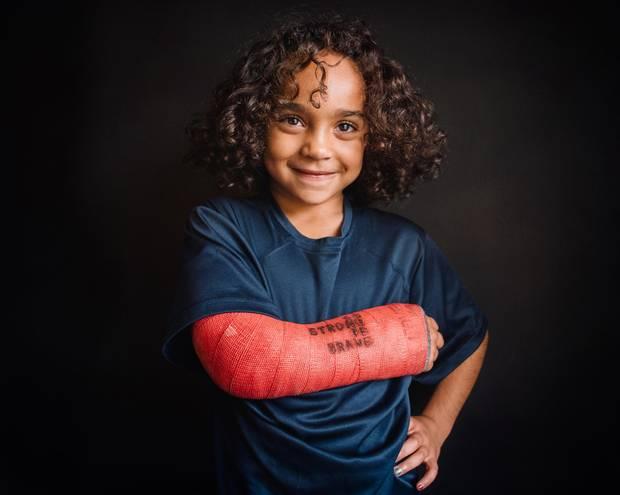Ein Mädchen zeigt stolz seinen Arm in rotem Gips
