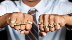 Rapper zeigt seine beiden geballten Fäuste mit Goldringen an den Fingern