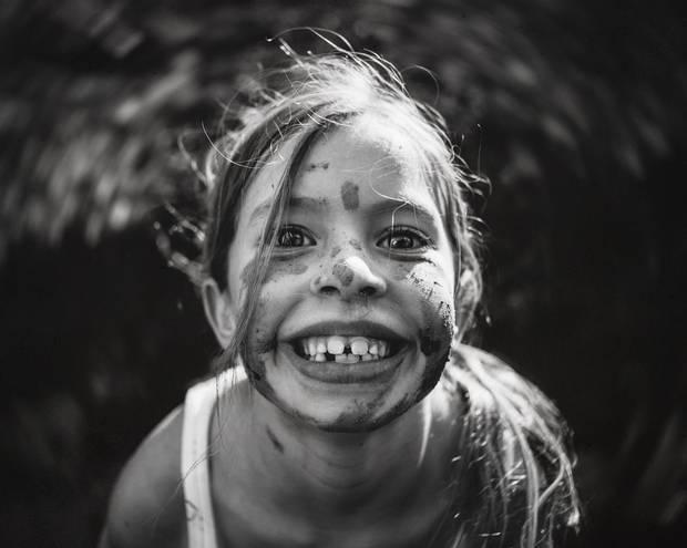 Ein Mädchen grinst mit dreckigem Gesicht in die Kamera
