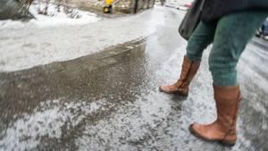Eine Frau geht bei Glatteis über eine Straße