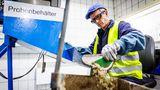 Weiterverarbeitung in der Glashütte: Ein Scherbeneingangskontrolleur entnimmt aus der Lieferung eine 50 Kilogramm schwere Probe und prüft die Qualität des Rohstoffs.