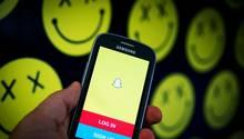 Die App Snapchat ist auf einem Samsung-Smartphone geöffnet, im Hintergrund sind morbide Smilys zu sehen