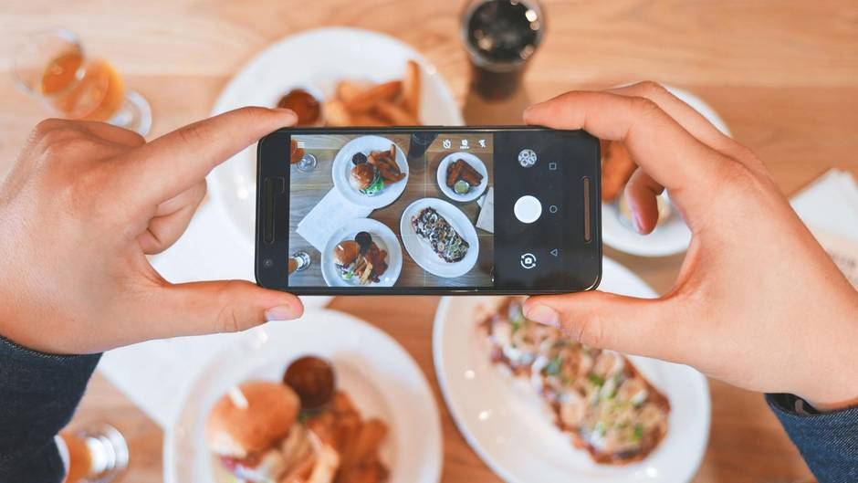 Jemand fotografiert mit seinem Handy sein Essen