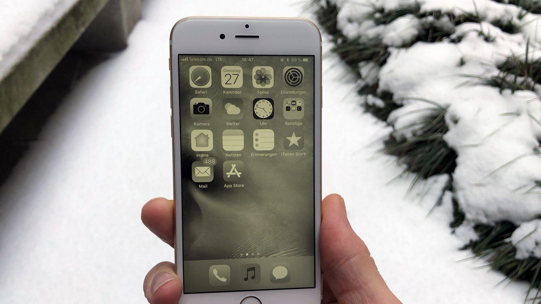 Ein iPhone zeigt vor verschneitem Hintergrund den Graustufen-Modus