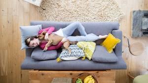 Junge Frau liegt entspannt auf grauem Sofa und kuschelt mit ihrem Hund