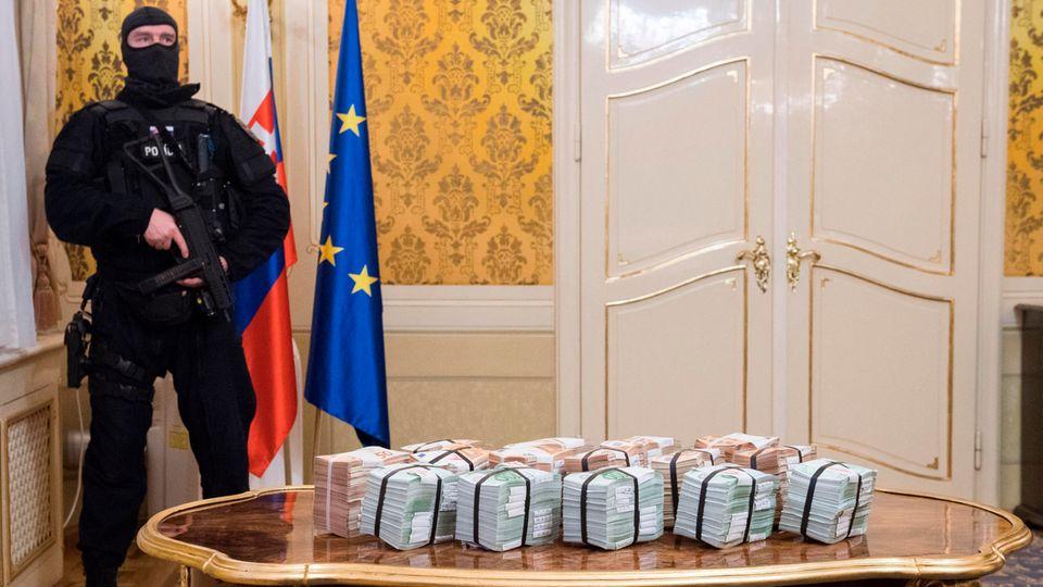 Bündel aus 50er und 100er Euro-Noten auf einem Tisch