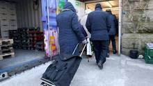 Kunden der Essener Tafel gehen mit ihren Einkaufswagen zur Lebensmittelausgabestelle.