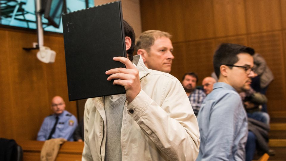 Angeklagter hält sich schwarze Mappe vor das Gesicht