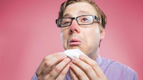Ein Mann niest in ein Taschentuch