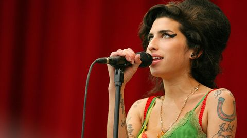 Amy Winehouse steht am Mikrofon und singt