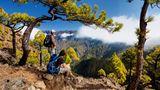 """La Palma  Morgens im Norden der Isla Bonita, der """"schönen Insel"""". Wer ein Stück weit oben wohnt, kann sehen, wie die Strahlen der Sonne langsam den Morgennebel aus der Caldera de Taburiente vertreiben, jenem gewaltigen Krater, der wirkt, als ob ihn ein vorzeitlicher Gigant voller Wut in das Gestein geschlagen hätte. Man kann die Caldera durch den Barranco de Las Angustias, die Schlucht der Ängste, durchwandern. Ein Erlebnis. Die ganze Insel ist ein Traum. Gerade für Wanderer: die Ausblicke spektakulär, die Vegetation üppig. Man findet jahrhundertealte, mächtige Drachenbäume, wandert durch den märchenhaften Dschungel des Biosphärenreservats von Los Tilos oder durch die 13 Tunnel von Marcos y Cordero zu malerischen Wasserfällen. Die Hauptstadt Santa Cruz lockt mit jahrhundertealter Architektur, der Ort Tazacorte mit einem schwarzen Sandstrand. Und abends nach der Wanderung dann ein kühles Bier in der """"heimlichen Hauptstad"""" Los Llanos auf der Plaza de España unter Lorbeerbäumen. Wandererglück!  Hacienda San Jorge bei Santa Cruz: Die Anlage in unmittelbarer Meeres nähe hat Dorfcharakter. DZ/F ab ca. 100 Euro, www.hsanjorge.com"""