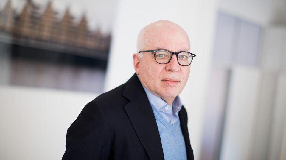 Michael Wolff, US-amerikanischer Autor, blickt mit nach rechts gedrehtem Kopf in die Kamera. Er trägt eine schwarze Brille