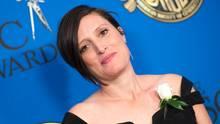 Eine weiße Frau mit schwarzem Bob steht im schwarzen, schulterfreien Kleid vor einer blauen Wand.
