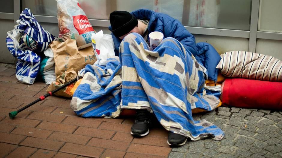 Ein Obdachloser sitzt eingehüllt in mehrere Decken auf der Straße