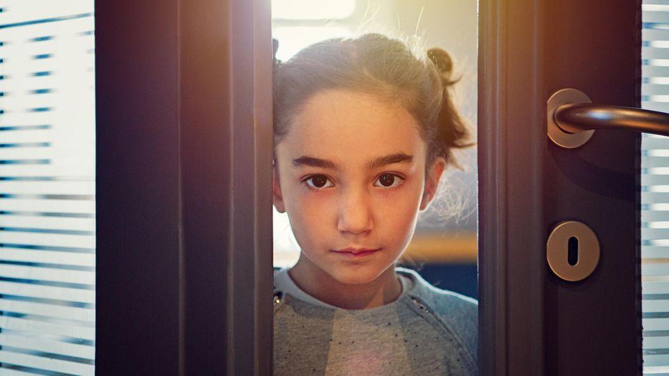 Ein Mädchen schaut durch einen Türspalt